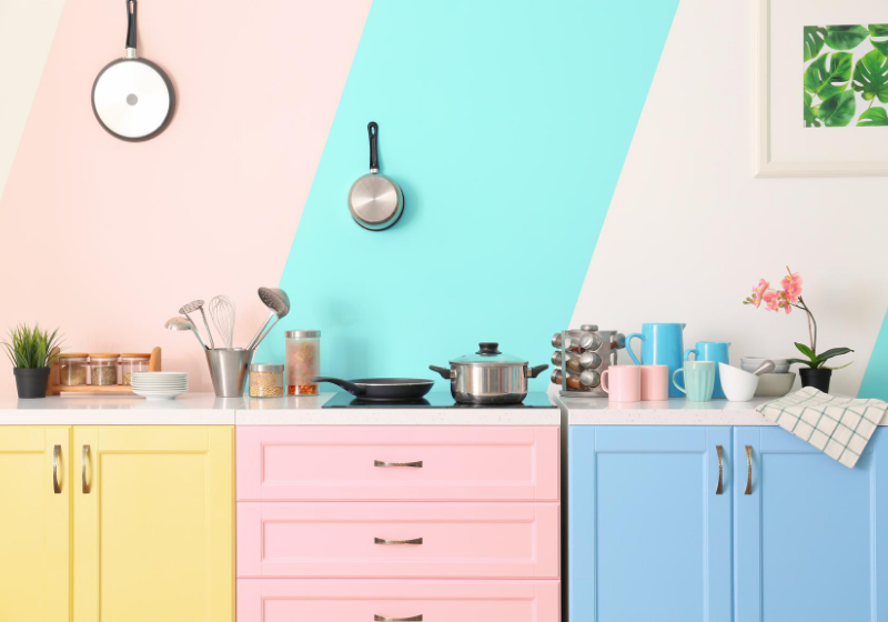 pink blue and yellow painted kitchen cupboards