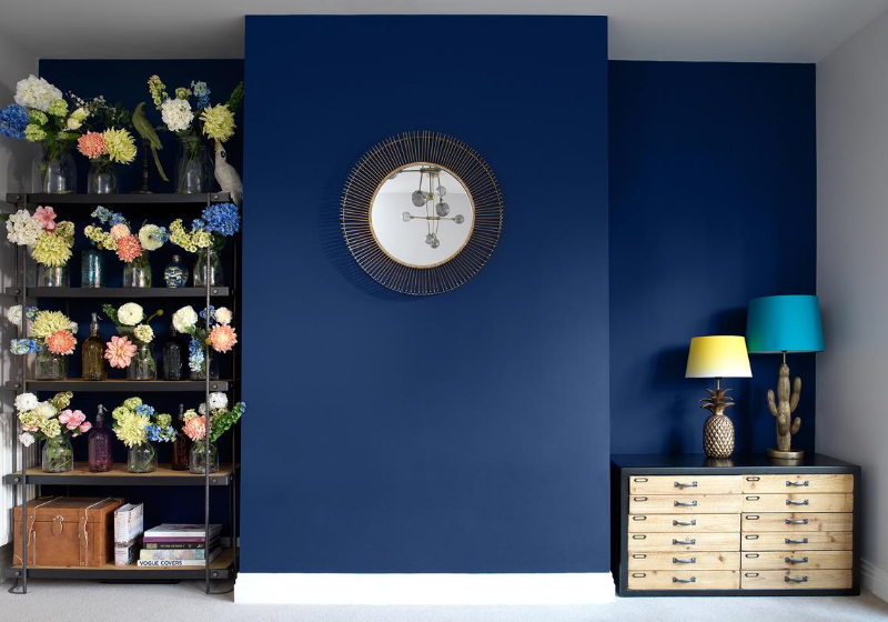 navy blue wall with vintage chest, gold mirror and flowers